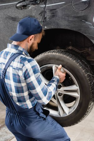 Photo for Back view of repairman in workwear fixing wheel on car - Royalty Free Image