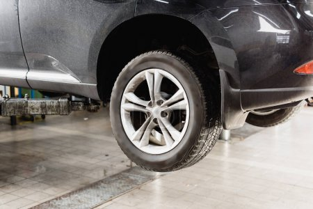 front wheels of modern car raised in workshop for maintenance