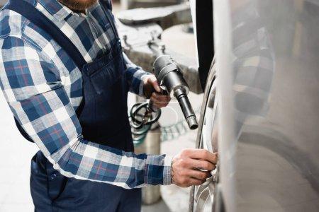 Photo pour Vue partielle du mécanicien en salopette réglant la roue de la voiture avec clé pneumatique au premier plan flou - image libre de droit