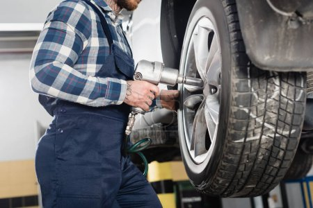 Photo for Cropped view of mechanic fixing wheel on car with pneumatic wrench - Royalty Free Image