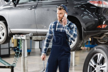 repairman holding wrench and talking on mobile phone near lifted car