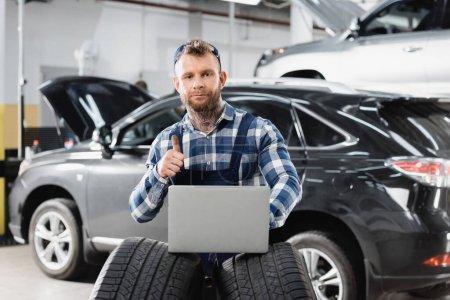 Reparaturarbeiter zeigt Daumen hoch, während er Laptop ordentliche Autos auf verschwommenem Hintergrund hält