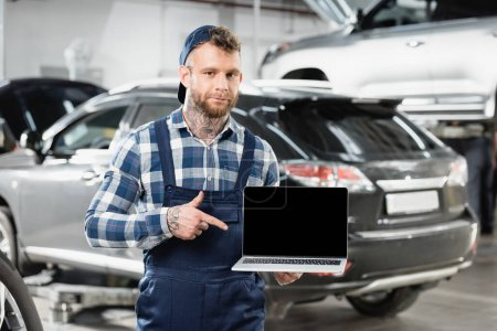 Photo for Repairman pointing at laptop with blank screen in workshop on blurred background - Royalty Free Image