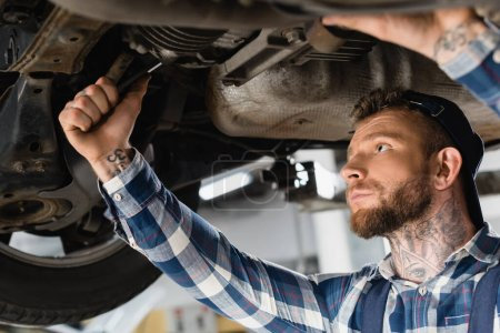 young technician checking bottom of lifted car with wrench