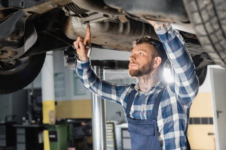 young repairman examining bottom of lifted automobile in workshop