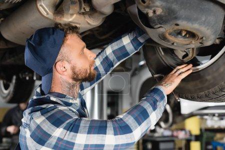 Photo pour Jeune technicien vérifier le fond de l'automobile soulevée dans l'atelier - image libre de droit