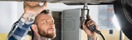 repairman fixing car detail with pneumatic wrench, banner