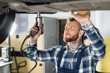 technician repairing bottom of lifted auto with pneumatic wrench on blurred foreground
