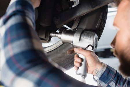 Photo pour Vue recadrée du technicien ajustant la roue de voiture avec clé pneumatique au premier plan flou - image libre de droit