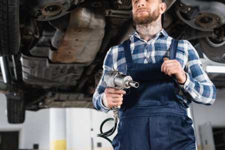 low angle view of technician holding pneumatic wrench near raised car on blurred background