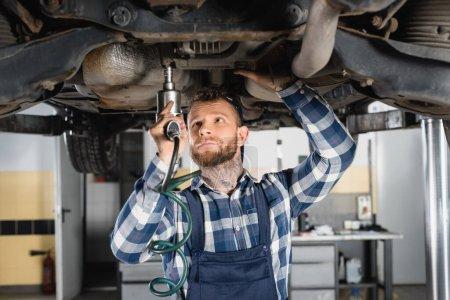 Photo pour Détail de fixation mécanique avec clé pneumatique tout en se tenant sous le wagon surélevé - image libre de droit