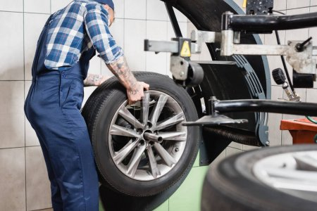 cropped view of technician examining wheel on balance control machine in garage on blurred foreground
