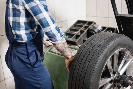 partial view of mechanic checking wheel on balance control equipment in workshop