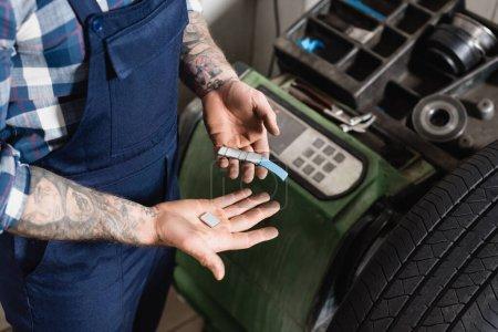 partial view of tattooed mechanic holding stripe with metallic balancing plates near balance control machine