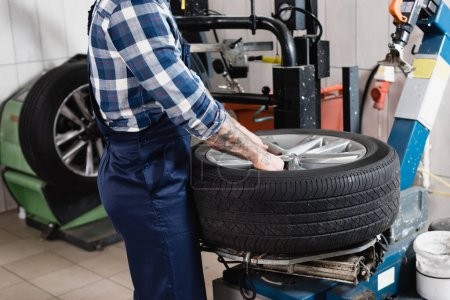 Photo for Cropped view of mechanic putting wheel on tire replacement machine in workshop - Royalty Free Image