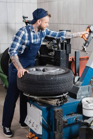young mechanic working with tire replacement machine in workshop