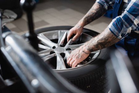 partial view of tattooed repairman taking car wheel in workshop on blurred foreground