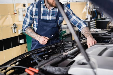 partial view of tattooed technician examining car engine compartment on blurred foreground