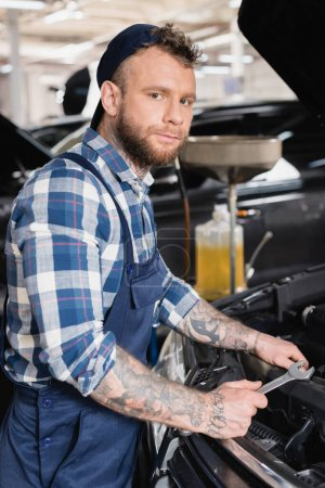 Photo for Tattooed mechanic holding wrench while standing near car engine compartment - Royalty Free Image