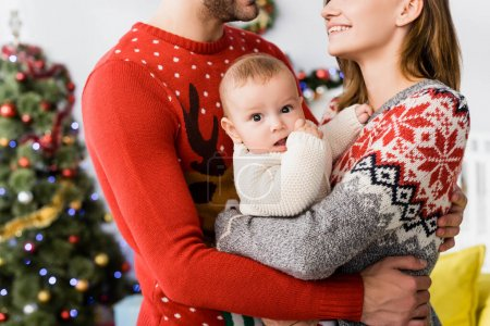 Photo for Infant boy in arms of mother near father and blurred christmas tree on background - Royalty Free Image
