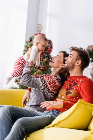happy woman holding in arms baby boy near husband in sweater and blurred christmas tree on background