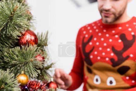 abgeschnittene Ansicht eines bärtigen Mannes im Pullover, der den Weihnachtsbaum auf verschwommenem Vordergrund schmückt