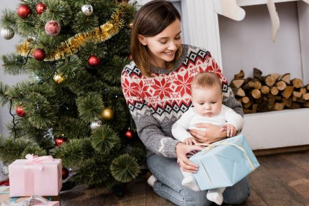 smiling woman holding present near infant son and decorated christmas tree