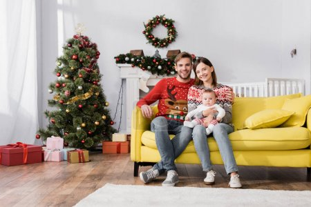 Photo for Happy family with baby boy sitting on sofa near christmas tree - Royalty Free Image