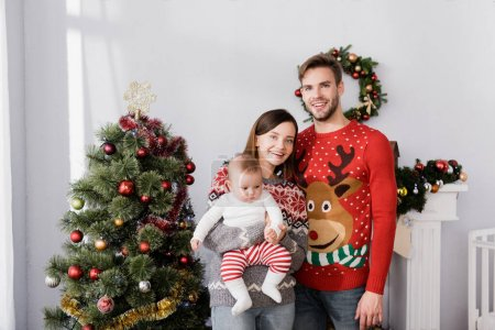 happy family with baby boy standing near christmas tree