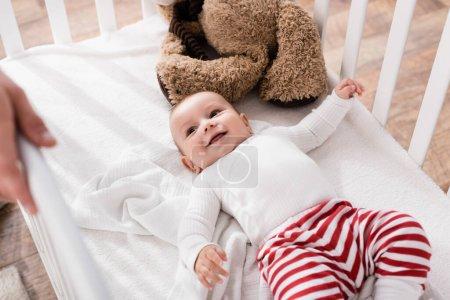Photo pour Heureux bébé garçon couché dans la crèche de bébé et regardant le père au premier plan flou - image libre de droit