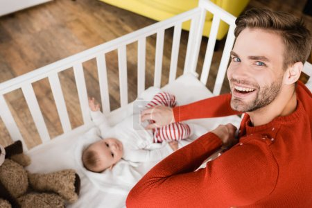 Photo for Happy father near infant son in baby crib on blurred background - Royalty Free Image
