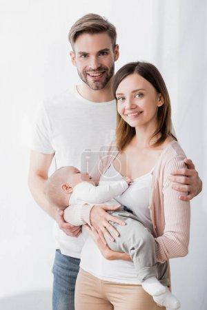 Photo pour Souriante femme tenant dans les bras bébé garçon près mari heureux - image libre de droit