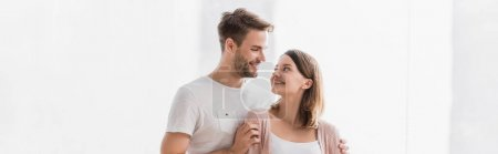 happy man and woman looking at each other while hugging at home, banner
