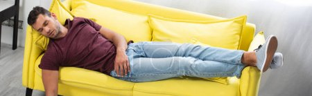 Young man sleeping on yellow couch at home, banner