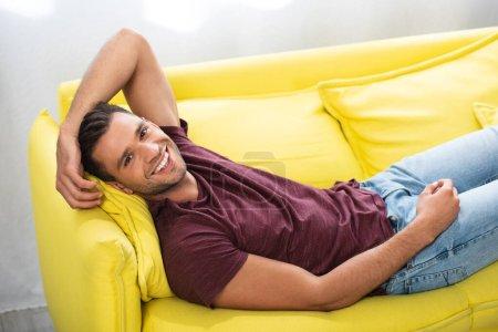 Photo pour Homme joyeux regardant la caméra tout en étant couché sur le canapé jaune à la maison - image libre de droit