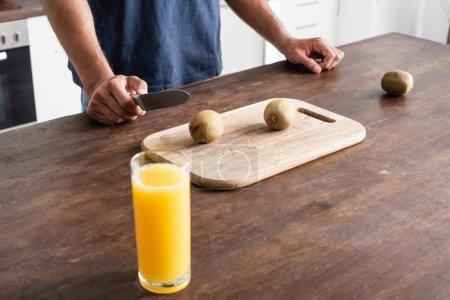 Photo pour Vue recadrée de l'homme tenant un couteau près du kiwi sur la planche à découper et un verre de jus d'orange au premier plan flou - image libre de droit