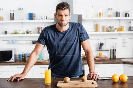Photo pour Triste homme regardant caméra près de jus d'orange, fruits et planche à découper sur la table - image libre de droit