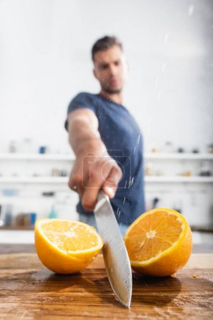Photo for Close up view of halves of orange and wet knife in hand of man on blurred background - Royalty Free Image