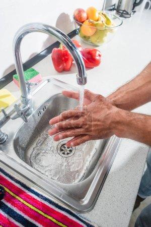 Photo pour Vue recadrée de l'homme se lavant les mains près des fruits et du paprika dans la cuisine - image libre de droit