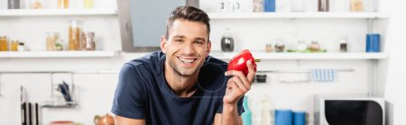 Cheerful man looking at camera while holding bell pepper, banner