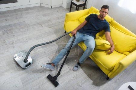 Photo pour Vue grand angle de l'homme tenant brosse d'aspirateur tout en étant assis sur le canapé à la maison - image libre de droit