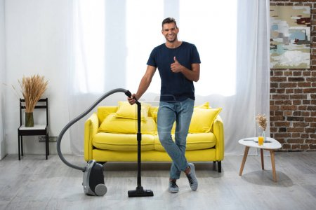 Photo for Smiling man showing thumb up while standing near vacuum cleaner in living room - Royalty Free Image