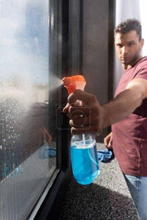 Photo pour Bouteille de détergent en main du jeune homme et fenêtre sur fond flou - image libre de droit