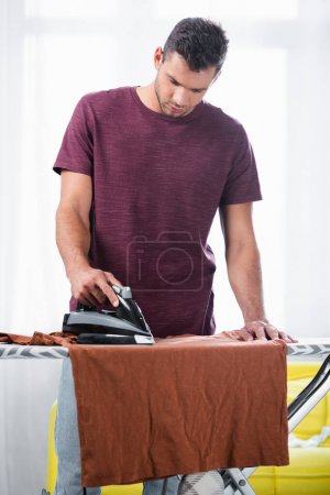 Young man ironing t-shirt on boat at home