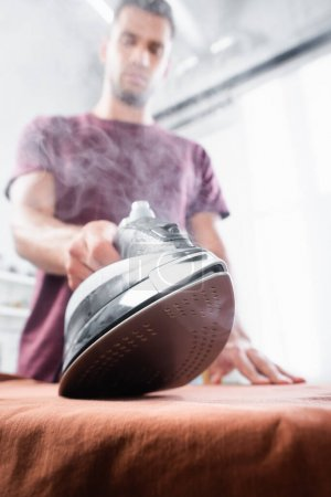 Photo pour Vue rapprochée du fer à repasser avec vapeur près des vêtements en main de l'homme sur fond flou - image libre de droit
