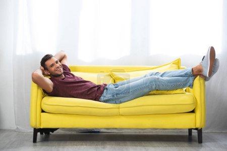 Photo pour Homme joyeux regardant la caméra tout en étant couché avec les jambes croisées sur le canapé - image libre de droit