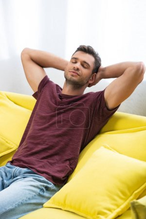 Photo for Young man with hands near head resting on couch at home - Royalty Free Image