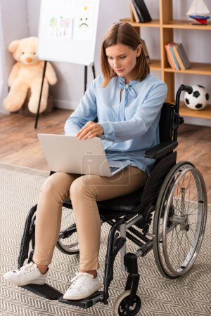 Photo for Full length of psychologist using laptop while sitting in wheelchair in office - Royalty Free Image