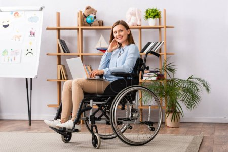 Photo for Full length of smiling psychologist with laptop looking at camera while sitting in wheelchair in office - Royalty Free Image