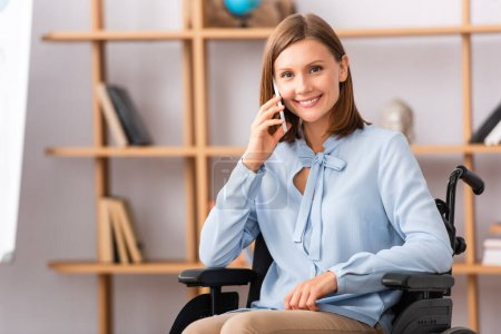 Photo for Smiling psychologist talking on mobile phone while sitting in wheelchair on blurred background - Royalty Free Image